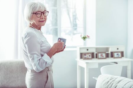 Pleasant grandmother. Cheerful pleasant elegant grandmother standing in cozy and light living room