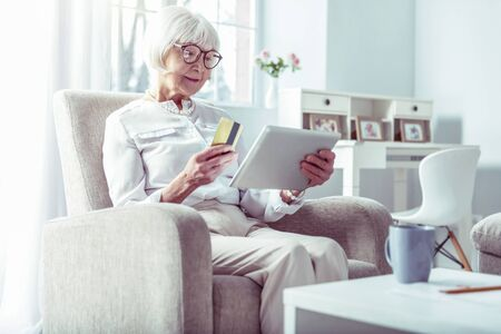 Shopping online. Modern retired woman holding bank card while shopping online via tablet sitting on beige sofa
