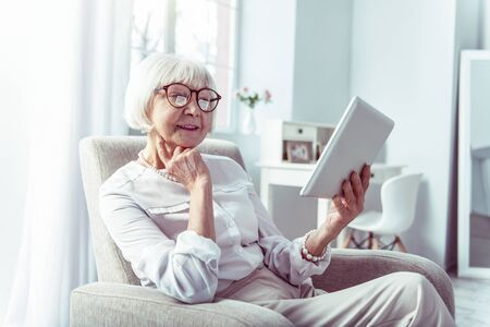 Family photos. Beaming elegant retired woman holding tablet feeling happy while watching family photos