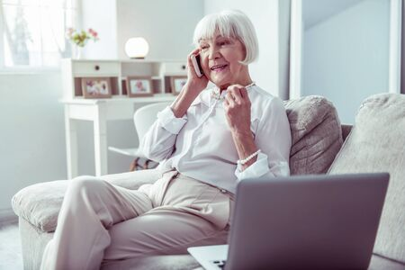Working woman. Working retired woman calling her business partner sitting on grey sofa near laptop Фото со стока