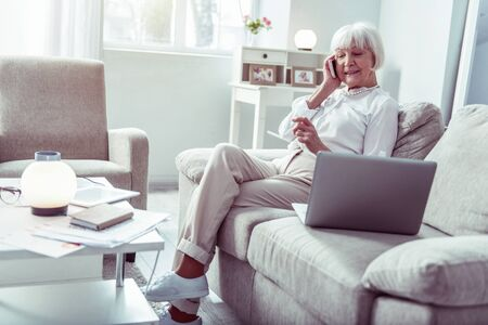 Receiving calls. Retired elegant stylish businesswoman sitting in living room receiving calls from partners Фото со стока