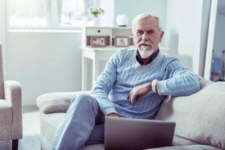 Cozy room. Blue-eyed bearded retired man wearing blue sweater sitting in light cozy living room Фото со стока