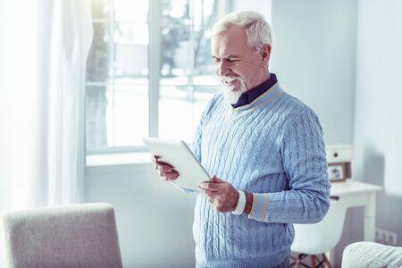 Modern technologies. Bearded grey-haired man enjoying modern technologies holding laptop and wearing smart watch