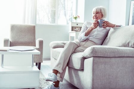 Waiting for husband. Retired woman wearing beige trousers and white blouse waiting for husband in living room
