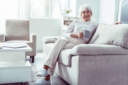 Beige sofa. Nice pleasant grandmother wearing white blouse sitting on beige sofa in living room