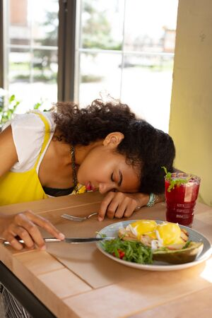 Falling asleep. Nice young woman lying on the table while falling asleep in the cafe