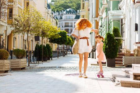 Be careful. Happy girl standing on skateboard while holding hand of her mother 스톡 콘텐츠