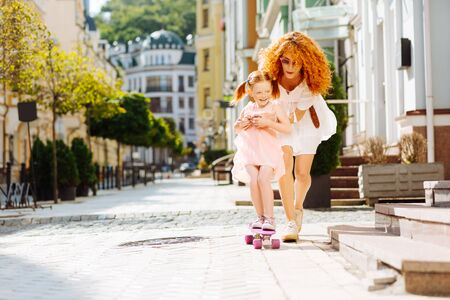 So happy. Amazing red-haired girl laughing while skating on board