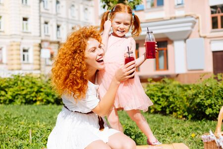 Loving relations. Pretty red haired female laughing at joke while spending weekend with her daughter Banco de Imagens
