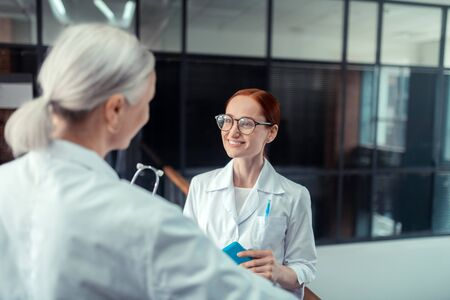 Red-haired doctor. Good-looking red-haired female doctor in eyeglasses smiling while looking at her colleague standing in the corridor