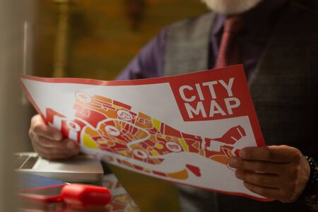Looking for the way. Bright city map in hands of bearded cafe visitor sitting at the table with his laptop on it. 스톡 콘텐츠