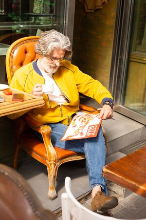 Reading the map. Bearded man sitting in the chair in the street cafe drinking coffee and looking at the city map.