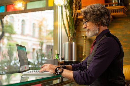 Working remotely. Concentrated bearded man sitting at the cafe table with his laptop working on his new project.