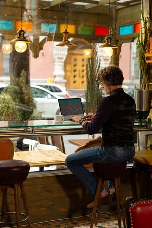 Focused on work. Serious adult man sitting at the cafe near the window table working on his laptop and drinking coffee. 스톡 콘텐츠
