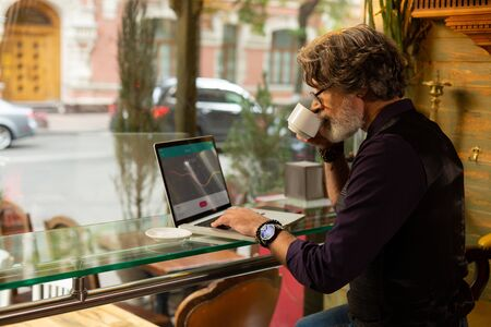 Working day. Handsome bearded man sitting near the big window in the caffee enjoying his coffee and working. 스톡 콘텐츠