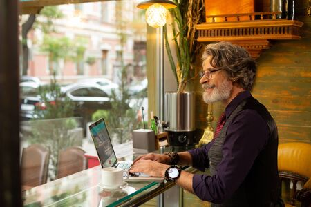 Working with joy. Smiling bearded man working on his laptop sitting in a coffee shop and looking out of the window. 스톡 콘텐츠