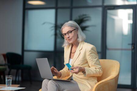 Debit card. Good-looking fashionable senior Caucasian woman sitting in an arm-chair in a modern office holding a debit card