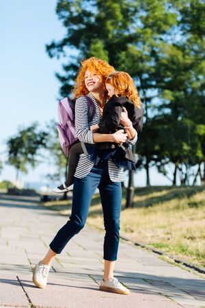 Happy mother. Pretty little girl embracing her mommy while being tired after classes Stok Fotoğraf