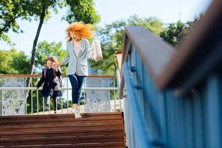 Active rest. Charming curly haired woman keeping smile on her face while walking with her child Stok Fotoğraf