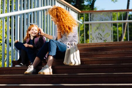 Friendly conversation. Delighted curly haired woman expressing positivity while having rest on stairs during walk Stok Fotoğraf