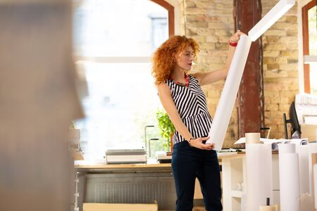 Stylish curly woman. Stylish curly woman working in publishing office wearing striped blouse while holding roll of paper