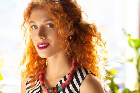 Beautiful woman. Stylish beautiful red-haired woman wearing necklace standing near window 免版税图像