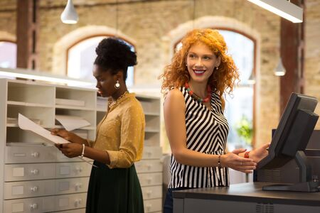 At cashier desk. Red-haired businesswoman sanding at cashier desk in stationery store