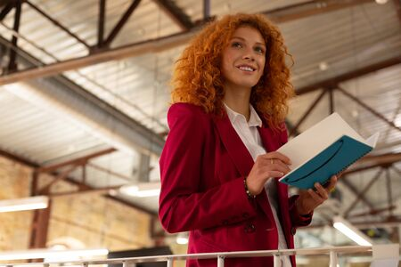 Inspired businesswoman. Inspired smiling businesswoman holding notebook while reading notes