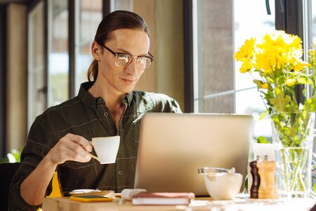 Energizing drink. Pleasant long haired man holding a cup with espresso while looking at the laptop screen