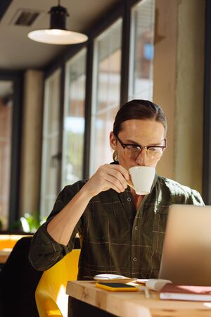 Best drink. Pleasant nice man sitting in front of his laptop while drinking coffee during his work Stok Fotoğraf