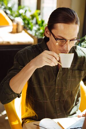 Fresh drink. Pleasant good looking man holding a cup while taking a sip of coffee Stok Fotoğraf