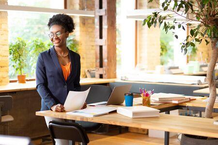 Spacious coworking. Interior designer wearing orange blouse working in spacious pleasant coworking