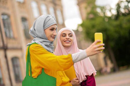 Women making selfie. Beautiful young muslim women wearing hijabs making selfie near university