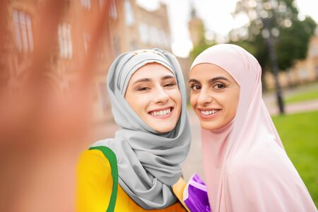 Smiling broadly. Appealing cheerful muslim students wearing hijabs smiling broadly