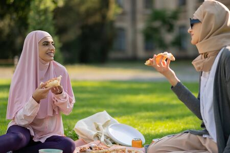 Students eating pizza. Muslim students eating pizza and talking after classes while sitting on grass Stock Photo
