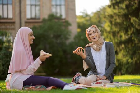 Enjoying lunch break. Muslim students wearing hijabs laughing and eating pizza enjoying lunch break