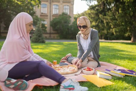 Hijab and sunglasses. Student wearing hijab and sunglasses having lunch with friend outside while eating pizza Stock Photo