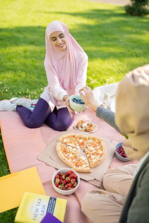 Lunch after studying. Appealing young women in hijabs eating pizza and fruits after studying