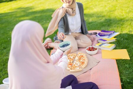 Blueberries after studying. Women in hijab taking blueberries after studying with friend outside Stock Photo