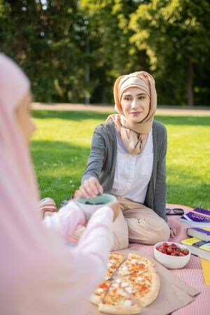 Lunch with friend. Beautiful muslim woman wearing hijab eating yummy lunch with friend Stock Photo