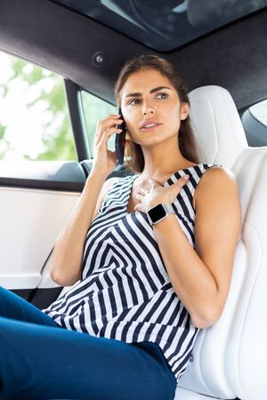 Calling secretary. Busy serious businesswoman calling her secretary while sitting in the car Stok Fotoğraf
