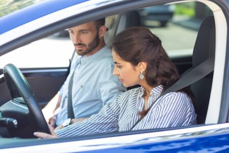 Wife driving. Dark-haired beautiful wife wearing striped blouse driving car while car sitting near her Standard-Bild