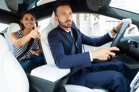 경로를 보여주는 아내. 그녀의 잘 생긴 수염 난 남편이 운전하는 동안 경로를 보여주는 웃는 아내 스톡 콘텐츠
