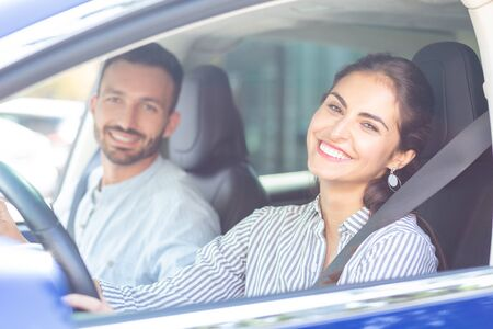 Wife smiling broadly. Beaming wife smiling broadly while driving car of her handsome bearded husband