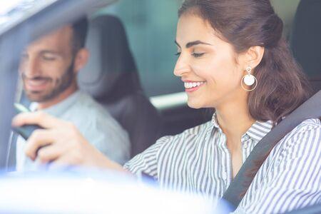 Wearing stylish earrings. Beautiful dark-haired wife wearing stylish earrings driving car sitting near husband