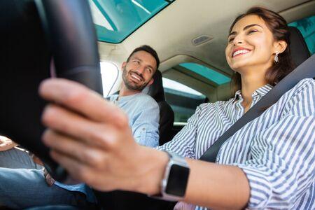 Holding steering wheel. Cheerful wife wearing smart watch holding steering wheel while driving