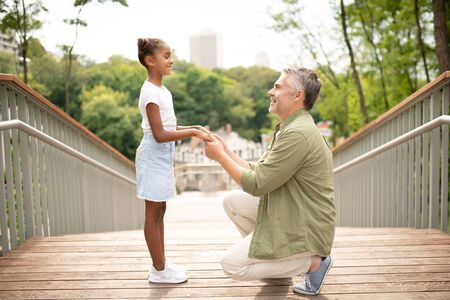 Speaking with daddy. Cheerful dark-skinned daughter smiling while speaking with daddy