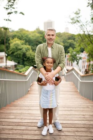 Near loving father. African-American adopted girl feeling good while standing near her loving father