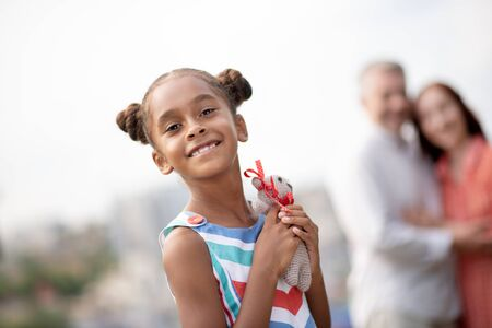 Happy daughter. Cheerful dark-skinned daughter feeling extremely happy after receiving toy