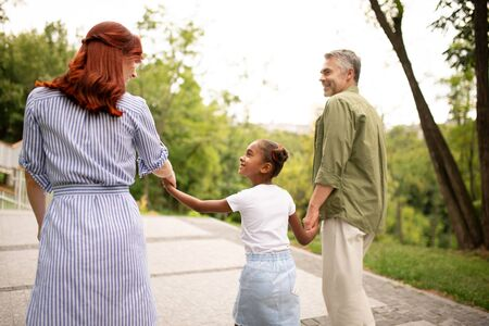 Woman with family. Red-haired happy woman looking at her lovely daughter and handsome husband Foto de archivo